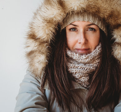 Close up of woman wearing winter clothing against white background.