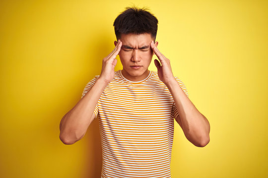 Young asian chinese man wearing t-shirt standing over isolated yellow background with hand on head for pain in head because stress. Suffering migraine.