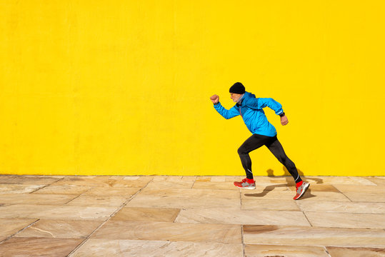 Side view of a senior man running against yellow wall in a bright day