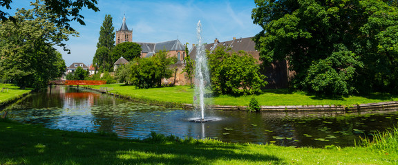 panorama view, canal with foutain and bridge, city wall, trees and church Grote Kerk in fortified city Vianen. The Netherlands