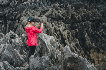 Side view of woman in protective helmet standing on rocky cliff and making picture by smartphone