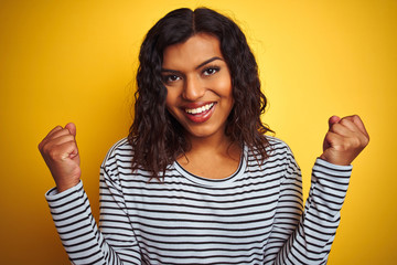 Transsexual transgender woman wearing striped t-shirt over isolated yellow background screaming proud and celebrating victory and success very excited, cheering emotion