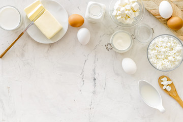 Fotobehang Zuivelproducten Fresh dairy products for breakfast with milk, cottage, eggs, butter, yougurt on white marble background top view mock up