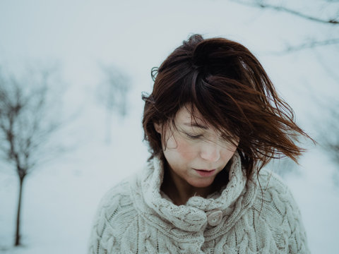 Close up of brunette woman standing on snowy landscape