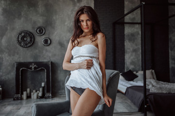 Beautiful brunette in sexy short white dress on dark background