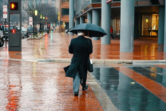 Elderly male person in a long coat walking with an umbrella during a rainy day