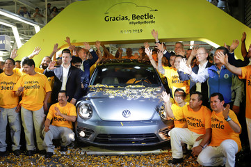 Employees pose for a picture next to a Volkswagen Beetle car during a ceremony marking the end of production of VW Beetle cars, at company's assembly plant in Puebla
