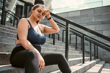 Tired after workout. Young plus size woman in sports clothing keeping eyes closed and touching her head while sitting on the stairs outdoors
