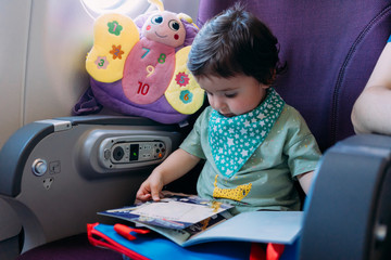 Toddler girl sitting on airplane watching picture book