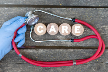 Doctor's or pharmacist's hand in blue glove holding stethoscope next to wooden cylinders with word care on old wood background. Health care to cure concept. Elderly volunteer's medical support.