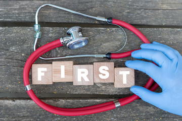 Doctor's hand touch wooden blocks with word first on old wood red stethoscope background. Health first safety.