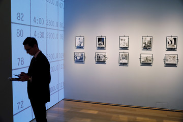"""A man stands in front of signed photographs from Apollo space missions that are displayed as part of Christie's upcoming """"One Giant Leap: Celebrating Space Exploration 50 Years After Apollo 11"""" auction in New York"""