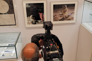 """A videographer films signed photographs of Apollo space missions are displayed as part of Christie's upcoming """"One Giant Leap: Celebrating Space Exploration 50 Years After Apollo 11"""" auction in New York"""