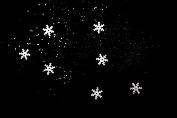 Abstract black background with isolated defocused snowflakes.