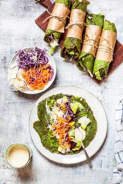 Lettuce wraps with spinach tortillas filled with lettuce, carrots and salad dressing