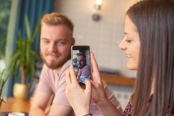 One girl talking a picture of a young man, on a smartphone. In a cafe.