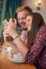 two friends sitting together, laughing while looking at a phone screen together.