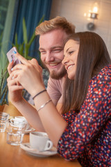 two friends sitting together, smiling while looking at a phone screen together.