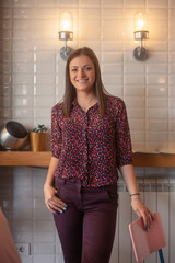 one young woman, standing in cafe, smiling.