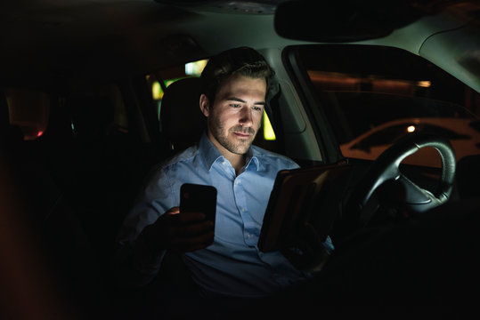 Young man using cell phone and tablet in car at night