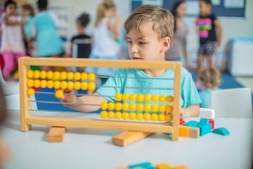 Boy in kindergarten using abacus