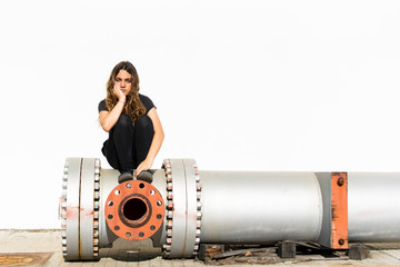 Portrait of serious teenage girl sitting on large pipe