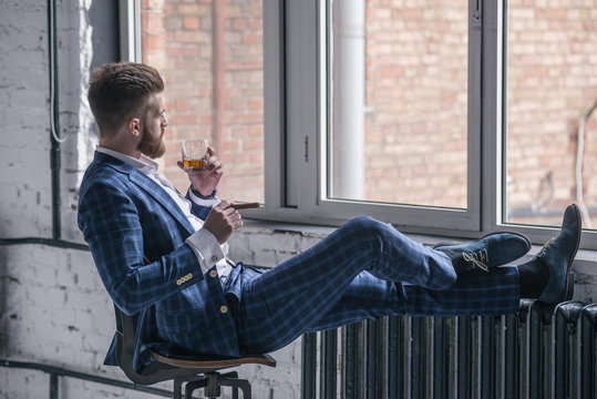 Handsome confident man is holding a cigar and a glass of whiskey and looking away while siting on the stool and looking to the window indoors. side view.
