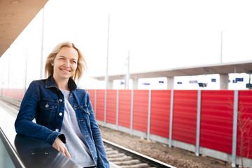 Smiling woman waiting at station platform