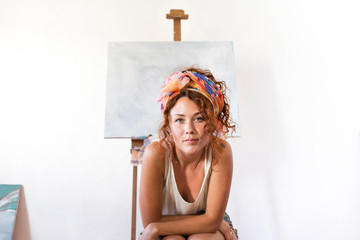 Portrait of young female painter in art studio next to empty canvas