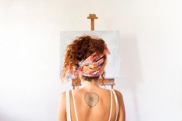 Rear view of young female painter in art studio in front of empty canvas