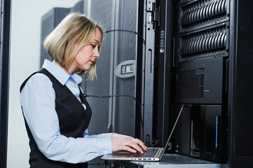 Cloud storage service. female engineer works with laptop in data center