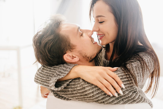 Close-up portrait of kissing couple spending morning together. Indoor photo of blissful european girl with long black hair hugging with husband on light background.
