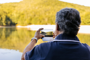 Back view of a senior man taking picture with mobile phone while contemplating amazing lake mountain landscape