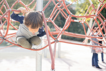 Pensive relaxed kid hanging on rope climbing net on playground in bright light