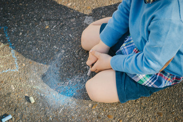 High angle view of boy drawing with chalk on asphalt