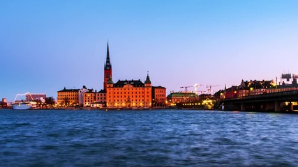 Wall Mural - Stockholm, Sweden. Time-lapse of Gamla Stan in Stockholm, Sweden with landmarks like Riddarholm Church during the sunrise. View of old buildings and cloudy sky in morning, panning video