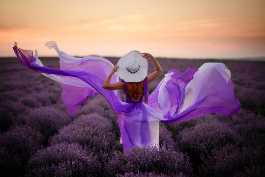 Young woman in luxurious purple dress standing in lavender field, rear view