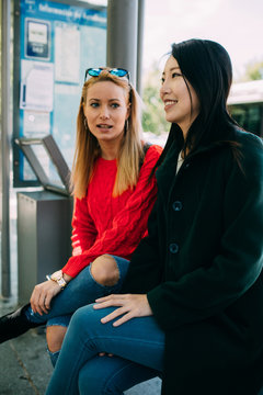 Young Asian woman and Caucasian friend sitting on bench and waiting for bus together
