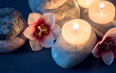 Spa with burning white candles standing on stones and flowers