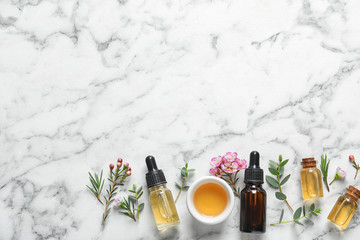 Flat lay composition with bottles of natural tea tree oil and space for text on white marble background Fototapete