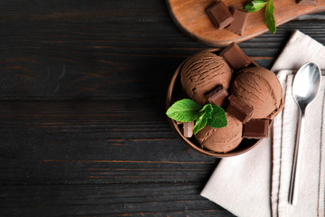 Flat lay composition with bowl of chocolate ice cream and mint on wooden table, space for text