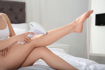 Woman doing leg epilation procedure on bed at home, closeup