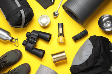 Flat lay composition with different camping equipment on color background