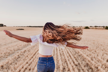 Summer Girl enjoying nature on yellow field. Beautiful young woman dancing Outdoors. Long hair in the wind. Happiness and lifestyle. Back view