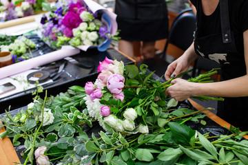 Obraz Female florist create a bouquet at workplace. Floristics workshop. Making beautiful flower bouquets and floral decorations.. - fototapety do salonu