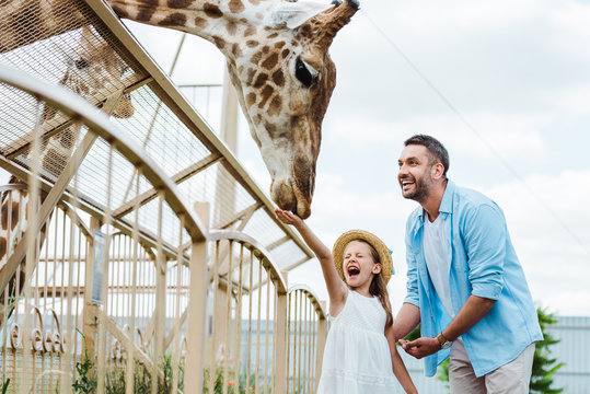 Selective focus of cheerful man and kid with closed eyes feeding giraffe in zoo