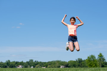 Happy young Asian girl jumping high in air, against background of summer blue sky.