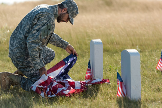 soldier in uniform and cap holding american flag while sitting in graveyard