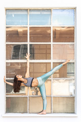Fit sporty active girl in fashion sportswear doing yoga fitness exercise in front of big industrial window frame. colorful reflections in window glass. Outdoor sports, urban style yoga.