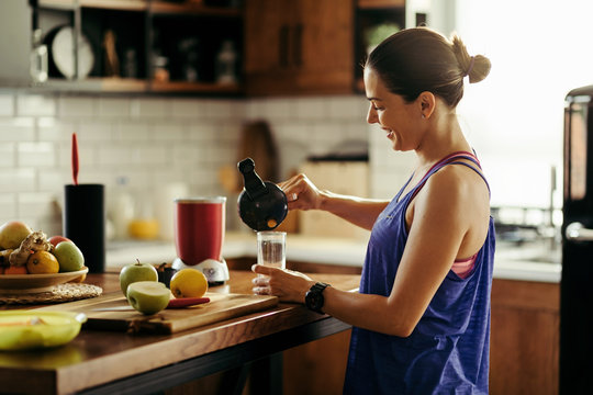 Happy sportswoman pouring herself fruit smoothie in the kitchen.